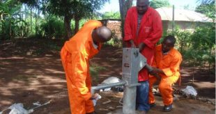 Men operating a borehole manually drilled by Simba Drilling Company. The human-powered drill can drill a six-inch borehole up to a depth of 250 feet.